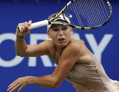 Caroline Wozniacki of Denmark returns a shot against Garbine Muguruza of Spain during their semifinals match of the Pan Pacific Open Tennis tournament in Tokyo, Saturday, Sept. 20, 2014. (AP Photo/Koji Sasahara)