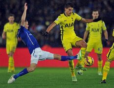 Leicester City's Paul Konchesky, left, tackles Tottenham Hotspur's Erik Lamela, right, during the English Premier League soccer match between Leicester and Tottenham Hotspur, at the King Power Stadium, in Leicester, Friday Dec. 26, 2014. (AP Photo/PA, Joe Giddens) UNITED KINGDOM OUT NO SALES NO ARCHIVE