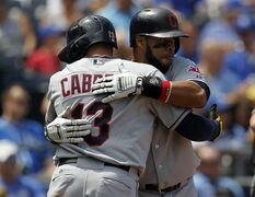 Cleveland Indians' Carlos Santana, right, hugs teammate Asdrubal Cabrera (13) at home plate after hitting a two-run home run in the fifth inning of a baseball game against the Kansas City Royals at Kauffman Stadium in Kansas City, Mo., Thursday, July 24, 2014. (AP Photo/Colin E. Braley)
