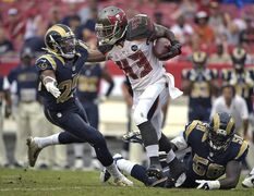 Tampa Bay Buccaneers running back Bobby Rainey (43) runs between St. Louis Rams defenders T.J. McDonald (25) and Jo-Lonn Dunbar (58) during the second quarter of an NFL football game Sunday, Sept. 14, 2014, in Tampa, Fla. (AP Photo/Phelan M. Ebenhack)