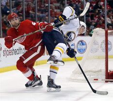 Detroit Red Wings' Jakub Kindl (4) knocks Buffalo Sabres' Luke Adam (72) off-balance during the first period of an NHL hockey game Friday, April 4, 2014, in Detroit. The Sabres have re-signed Adam to a one-year, two-way contract, which provides them the option to have him play in the minors THE CANADIAN PRESS/AP/Duane Burleson