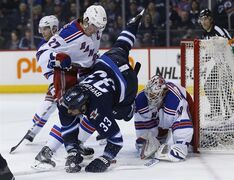 Winnipeg Jets' Dustin Byfuglien (33) is checked by New York Rangers' Ryan McDonagh (27) as goaltender Henrik Lundqvist (30) keeps his eye on the puck during second period NHL action in Winnipeg on Tuesday, March 31, 2015. Byfuglien is facing a suspension of up to five games after delivering a vicious cross-check to the back of New York Rangers centre J.T. Miller on Tuesday night. THE CANADIAN PRESS/John Woods