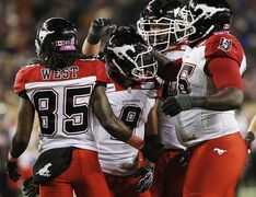 Calgary Stampeders' Jon Cornish (9) celebrates his touchdown against the Winnipeg Blue Bombers with Joe West (85), Stanley Bryant (66), and Shane Bergman (60) during the second half of CFL action in Winnipeg Saturday, October 18, 2014. Cornish was named CFL offensive player of the week and top Canadian after his stellar performance in the Stampeders' 33-23 victory over the Blue Bombers. THE CANADIAN PRESS/John Woods