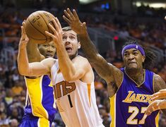 Phoenix Suns guard Goran Dragic puts a shot up between Los Angeles Lakers Wesley Johnson, left, and Jordan Hill during the first half of their NBA basketball game Wednesday, Oct. 29, 2014 in Phoenix. (AP Photo/The Arizona Republic, Michael Chow) MARICOPA COUNTY OUT; MAGS OUT; NO SALES