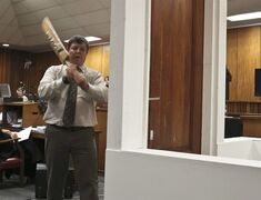 Forensic investigator Johannes Vermeulen, with a cricket bat in hand, demonstrates on a mock-up toilet and door in Pretoria, South Africa, March 12, 2014. THE CANADIAN PRESS/AP, Alexander Joe