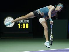 Canada's Eugenie Bouchard serves to Serbia's Ana Ivanovic during their singles match at the WTA tennis finals in Singapore,Wednesday, Oct. 22, 2014. (AP Photo/Mark Baker)