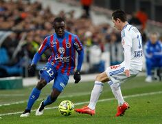 Caen's defender Dennis Appiah, left, challenges for the ball with Marseille's French midfielder Florian Thauvin , during the League One soccer match between Marseille and Caen, at the Velodrome Stadium, in Marseille, southern France, Friday, Feb. 27, 2015. (AP Photo/Claude Paris)
