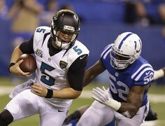 Jacksonville Jaguars quarterback Blake Bortles (5) is chased by Indianapolis Colts inside linebacker D'Qwell Jackson (52) during the second half of an NFL football game Sunday, Nov. 23, 2014, in Indianapolis. (AP Photo/Michael Conroy)