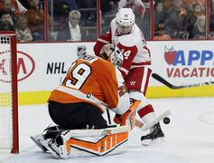 Philadelphia Flyers' Ray Emery (29) left, defends the goal as Detroit Red Wings' Gustav Nyquist (14) is unable score in the third period of an NHL hockey game Saturday, Oct. 25, 2014, in Philadelphia. The Flyers won 4-2. (AP Photo/Tom Mihalek)