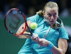 Petra Kvitov of the Czech Republic makes a backhand return to Poland's Agnieszka Radwanska during their singles match at the WTA tennis finals in Singapore,Tuesday, Oct. 21, 2014. (AP Photo/Mark Baker)
