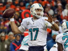 As snow falls, Miami Dolphins quarterback Ryan Tannehill (17) throws against the Denver Broncos during the first half of an NFL football game, Sunday, Nov. 23, 2014, in Denver. (AP Photo/Jack Dempsey)