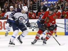 Winnipeg Jets right wing Michael Frolik (67) and Chicago Blackhawks defenseman Niklas Hjalmarsson (4) battle for a bouncing puck during the first period of an NHL hockey game Tuesday, Dec. 23, 2014, in Chicago. (AP Photo/Charles Rex Arbogast)