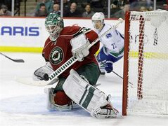 Minnesota Wild goalie Josh Harding (37) deflects a shot by the Vancouver Canucks during the second period of an NHL hockey game in St. Paul, Minn., Tuesday, Dec. 17, 2013. Harding has a broken right foot, putting him out indefinitely. THE CANADIAN PRESS/ AP/Ann Heisenfelt