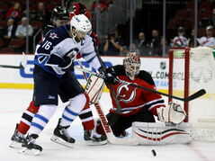 Winnipeg Jets' Andrew Ladd (16) battles with New Jersey Devils' Marek Zidlicky (2) in front of goaltender Cory Schneider (35) during first period NHL hockey action at the Prudential Center in Newark, N.J., Thursday.