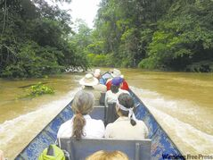 The group heads down the Ecuadorian Amazon in a motorized canoe.