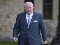 Sen. Mike Duffy arrives to the Senate on Parliament Hill in Ottawa, Monday, October 28, 2013. The NDP is asking Canada's director of public prosecutions to look at the evidence collected by the RCMP in the Duffy case to determine if charges should be laid against other people as well. THE CANADIAN PRESS/Adrian Wyld