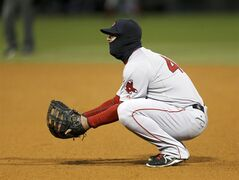 Wearing a balaclava, Boston Red Sox first baseman Mike Napoli takes a defensive stance during the sixth inning of a baseball game against the Chicago White Sox on Tuesday, April 15, 2014, in Chicago. Temperatures were in the mid-30s for the game. (AP Photo/Charles Rex Arbogast)