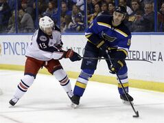 St. Louis Blues' Barret Jackman, right, passes the puck as Columbus Blue Jackets' Cam Atkinson defends during the first period of an NHL hockey game Saturday, March 28, 2015, in St. Louis. (AP Photo/Jeff Roberson)