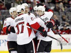 Ottawa Senators players celebrate after center Kyle Turris (7) scored a goal against the New Jersey Devils during the first period of an NHL hockey game, Wednesday, Dec. 17, 2014, in Newark, N.J. (AP Photo/Julio Cortez)