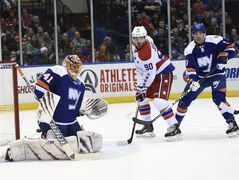 New York Islanders defenseman Travis Hamonic (3) and Washington Capitals left wing Marcus Johansson (90) watch the puck shot by Capitals left wing Alex Ovechkin get past New York Islanders goalie Jaroslav Halak (41) to score in the first period of an NHL hockey game at Nassau Coliseum on Wednesday, Nov. 26, 2014, in Uniondale, N.Y. (AP Photo/Kathy Kmonicek)