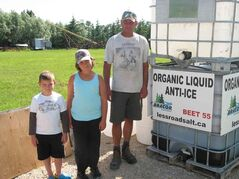 Corey Bossuyt (right), with nephew Riley and niece Alexis, stands next to a container of Beet 55, the liquid de-icer that Bossuyt and his brother Brad make, use and market.