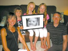 From left to right: Kristen, Aria, Maya, Calla and Michael with a portrait of baby Georgia, who died in 2009. Georgia had Type 1 spinal muscular atrophy.