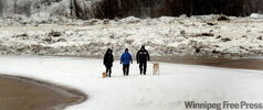 Residents of the RM of St. Andrews walk along Red River Drive in front of a huge ice jam that has caused the Red River to overflow its banks.