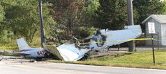 The wreckage from a plane that crashed rests on the side of a road, Tuesday, Aug. 26, 2014, in Richmond Heights, Ohio. The Cessna 172R crashed and burst into flames just after takeoff Monday night from Cuyahoga County Airport, outside of Cleveland, killing all four people on board, according to the Ohio State Highway Patrol. (AP Photo/The Plain Dealer, Chuck Crow) MANDATORY CREDIT; NO SALES