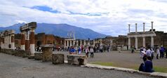 In this May 14, 2014 photo, tourists stroll past the remains of Pompeii's forum. The ancient town of Pompeii, located near modern-day Naples, Italy, was destroyed in A.D. 79 following the eruption of Mount Vesuvius. An estimated 2.5 million people visit the site each year. (AP Photo/Michelle Locke)