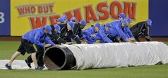 The New York Mets grounds crew rolls out the tarp to cover the field as rain begins to fall during the fourth inning of a baseball game against the Arizona Diamondbacks, Friday, May 23, 2014, in New York. (AP Photo/Julie Jacobson)
