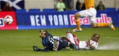 New York Red Bulls goalkeeper Luis Robles, left, and defender Jamison Olave, bottom, slide to stop the attack of Houston Dynamo's David Horst during the second half of an MLS soccer game on Wednesday, April 23, 2014, in Harrison, N.J. The Red Bulls won 4-0. (AP Photo/Julio Cortez)