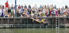 Competitors battle one another with a sponge filled sack, while sitting on a soap covered beam over Gimli Harbour during the Islendingadunk competition Saturday.