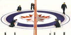 A work crew lays down the Jets logo at centre ice in the MTS Centre Tuesday. The Jets will open the abbreviated season Jan. 19 at home against the Ottawa Senators.