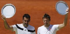 Daniel Nestor from Canada, right and Nenad Zimonjic from Serbia , left, hold their trophies after a Madrid Open tennis tournament doubles final match against Bob Bryan and Mike Bryan from the U.S, in Madrid, Spain, Sunday, May 11, 2014. (AP Photo/Andres Kudacki)