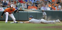 Baltimore Orioles third baseman Manny Machado, left, waits for the throw as Tampa Bay Rays' Ben Zobrist slides safely into third on a triple in the ninth inning of a baseball game, Saturday, June 28, 2014, in Baltimore. The Rays won 5-4. (AP Photo/Gail Burton)