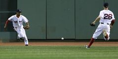 Boston Red Sox center fielder Mookie Betts, left, and right fielder Brock Holt chase down a double by Los Angeles Angels' Kole Calhoun during the eighth inning of a baseball game at Fenway Park in Boston, Monday, Aug. 18, 2014. (AP Photo/Charles Krupa)