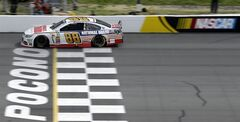 Dale Earnhardt Jr. (88) crosses the start/finish line during the NASCAR Sprint Cup series Pocono 400 auto race, Sunday, June 8, 2014, in Long Pond, Pa. Earnhardt Jr. won the race. (AP Photo/Mel Evans)