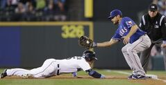 Seattle Mariners' Kyle Seager, left, dives back to first as Texas Rangers first baseman Brad Snyder catches the ball on a pickoff-attempt in the second inning of a baseball game on Sunday, June 15, 2014, in Seattle. Seager, who singled earlier, was safe. (AP Photo/Elaine Thompson)