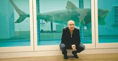 Damien Hirst beside his 1991 piece -- a tiger shark peserved in formaldehyde.)