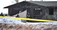 Charlottetown firefighters hold a tarp as officials remove bodies from an abandoned building fire in Charlottetown, P.E.I., Saturday, March 29, 2014. THE CANADIAN PRESS/Nathan Rochford