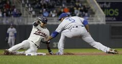 Minnesota Twins' Eduardo Escobar, left, slides into the tag by Los Angeles Dodgers third baseman Juan Uribe, right, and is out at third while attempting to stretch a double into a triple during the second inning of a baseball game in Minneapolis, Wednesday, April 30, 2014. (AP Photo/Ann Heisenfelt)