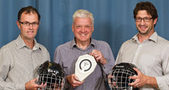 Dr. Wayne Hildahl (centre) holds a scale, which is used in conjunction with the hockey helmets held by Drs. Peter MacDonald (left) and Jeff Leiter, to test the neck strength of young athletes.