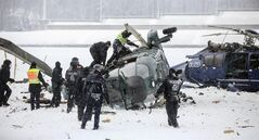 Rescue workers examine two crashed helicopters of the German federal police on a field at the Olympic Stadium in Berlin, Germany, March 21,2013. The two helicopters collided as they approached for landing during an exercise of the federal police .(AP Photo/dpa/ Hannibal Hanschke)
