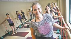 Heather Senderewich, manager of Moksha Yoga, teaches a barre class.