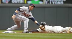 Minnesota Twins' Brian Dozier slides into the tag by Detroit Tigers shortstop Andrew Romine, left, and is out stealing second base during the third inning of a baseball game in Minneapolis, Saturday, April 26, 2014. Dozier was initially ruled safe but after a review was called was ruled out. (AP Photo/Ann Heisenfelt)