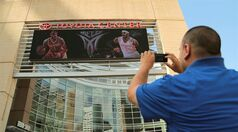 Houston Rockets fan Frank Vasquez takes a photograph of free agent forward Carmelo Anthony wearing Rockets jerseys in composite images on the Toyota Center marquee on Wednesday, July 2, 2014, in Houston. Anthony was wearing his No. 7 in both renderings, despite the fact that current Rocket Jeremy Lin wears that number. The Rockets would likely have to unload the point guard to snag Anthony. (AP Photo/Houston Chronicle, Billy Smith II) MANDATORY CREDIT