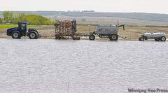 Farm equipment sits in a flooded field south of Deloraine, Man., Wednesday.