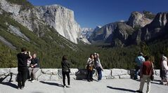 File - In this Oct. 17, 2013 file photo, visitors at Tunnel View, like Kaori Nishimura and Eriko Kuboi, from Japan, center facing, enjoy the views of Yosemite National Park, Calif. Tunnel View is a scenic vista which shows off El Capitan, Half Dome and Bridalveil Fall. Yosemite National Park is celebrating the 150th anniversary of President Abraham Lincoln's signing of the Yosemite Grant Act, Monday June 30, 2014, which protected Yosemite Valley and Mariposa Grove. (AP Photo/Gary Kazanjian, File)