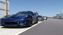 In this photo made from video, a Corvette Z06, Lotus Exige S240, McLaren MP4-12C and Ferrari F430 Suderia, from left, line up in the pit area of Atlanta Motorsports Park, Thursday, April 17, 2014, in Dawsonville, Ga. The track is the only motorsports country club in the South providing the well-heeled with road racing services for their exotic cars. (AP Photo/Johnny Clark)