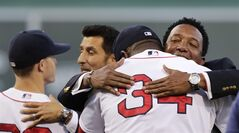Boston Red Sox great Pedro Martinez, right, embraces designated hitter David Ortiz after throwing out the ceremonial first pitch prior to a baseball game at Fenway Park in Boston, Thursday, Aug. 14, 2014. Martinez, Nomar Garciaparra and Roger Clemens were inducted into the Boston Red Sox Hall of Fame earlier in the day. (AP Photo/Charles Krupa)